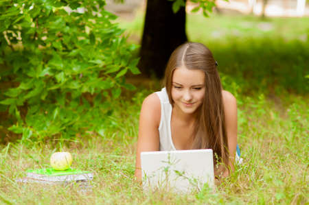 tree works: Teen girl works with the laptop on the grass near the tree Stock Photo