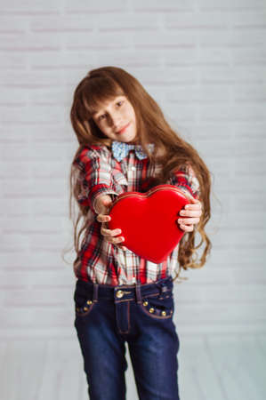 Little girl with a red box of chocolates in a heart shape photo