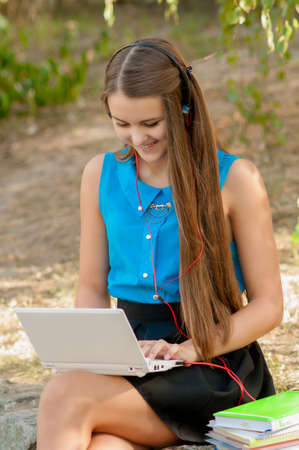 southern european descent: Teen girl works with the laptop in headphones and books sitting on the curb Stock Photo