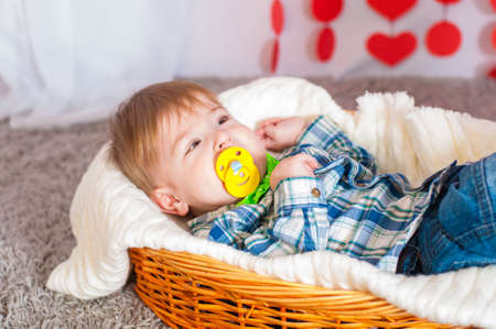 Child in the bow tie is in the basket with a blanket