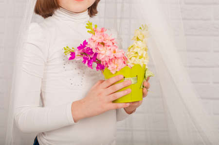 baby 4 5 years: hands of a little girl with spring flowers in a vase