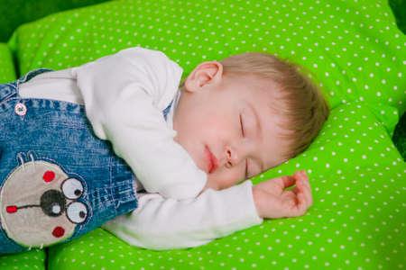 oversleep: Little baby sleeping on a green cushion