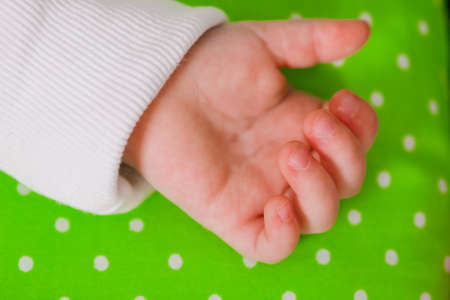 laying forward: Hand of a little baby sleeping on a green cushion