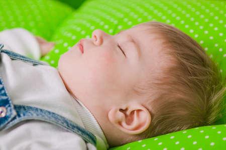 laying forward: Little baby sleeping on a green cushion