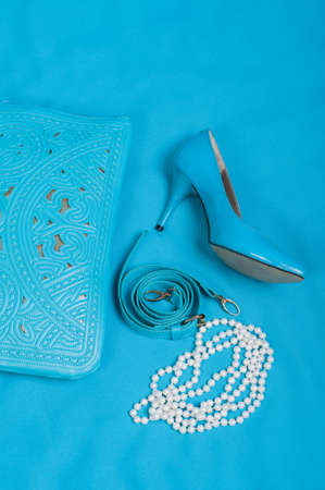 no heels: Beautiful blue shoes and handbag, pearls on blue background Stock Photo