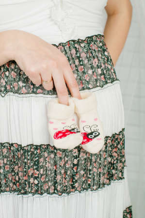 Baby socks in the hands of pregnant woman photo