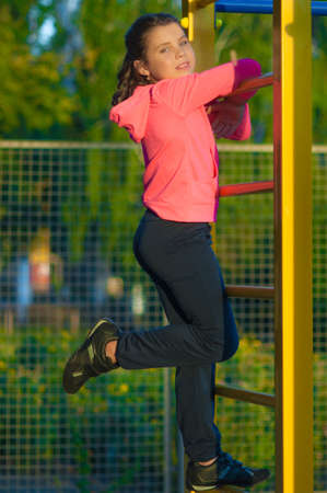 man in air: Little girl in sportswear on the playground in the summer