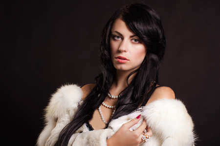 white fur: Beautiful girl with dark hair in a white fur coat with pearls Foto de archivo