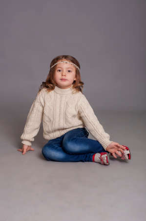 hispanic girl: Little girl in white sweater and blue jeans