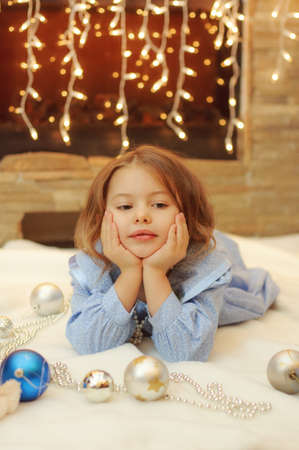Little girl at home by the fireplace with Christmas balls