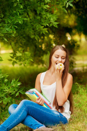 southern european descent: Girl student with books on the grass eating an apple