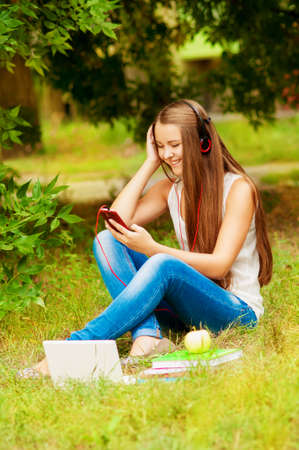 southern european descent: Girl student on the grass in headphones with  phone and computer