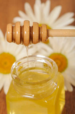 spoonful: jar of honey and a spoonful of honey with daisies