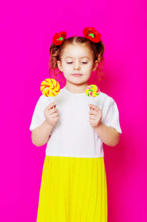 fruit candy: Little girl in a beautiful dress with a big candy lollipop in hands
