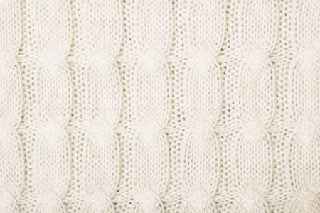 knotted: White knitted texture with ornament braid Stock Photo