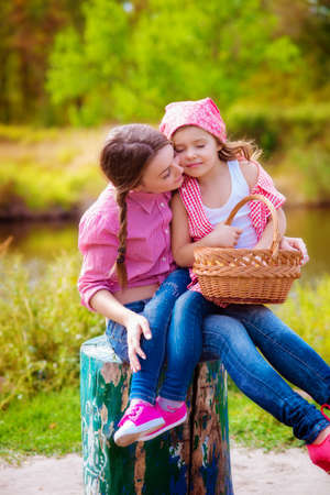 The girl and her younger sister in the nature near the river in autumn Stock Photo