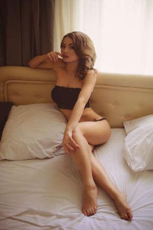 donna completamente nuda: Bella ragazza sexy con capelli lunghi in lingerie sul letto in camera da letto Archivio Fotografico