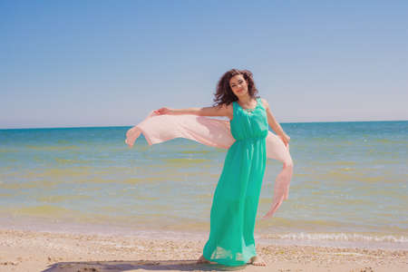 scarf beach: Young girl on the beach in summer in a beautiful dress with a flying scarf in hands