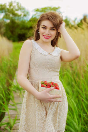Girl with long hair  in summer with strawberries Stock Photo