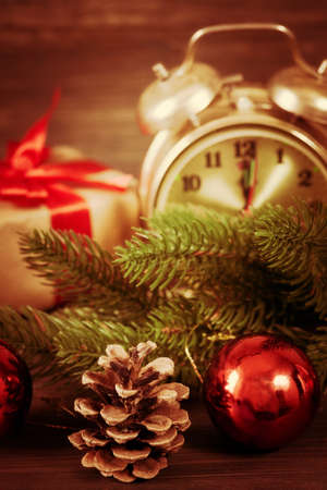 Christmas decoration with retro alarm clock, Santa Claus hat, baubles and pine cone with branch on a wooden wall background