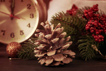 twelfth night: Christmas decoration with retro alarm clock, Santa Claus hat, baubles and pine cone with branch on a wooden wall background