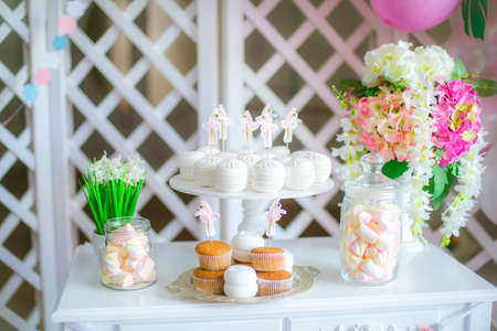 Candy bar in pink colors for a childrens party. Decorated with airy bright balloons baby candy bar
