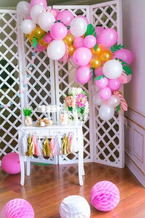 子供のパーティーのためのピンク色の棒キャンディ。風通しの良い明るい風船赤ちゃんお菓子バーで飾られました。