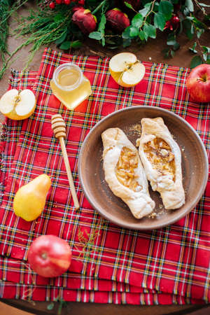 Baking with autumn fruits and honey. A table with autumn delicious. Apple pie with honey Stock Photo