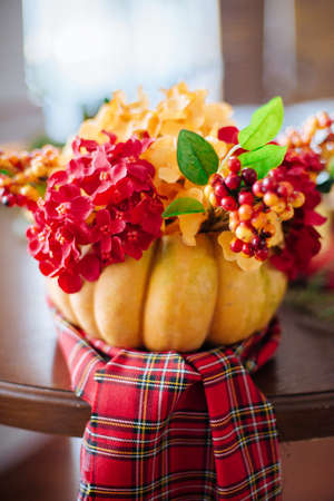 Autumn composition of a pumpkin with flowers. Table with autumn fruits and vegetables