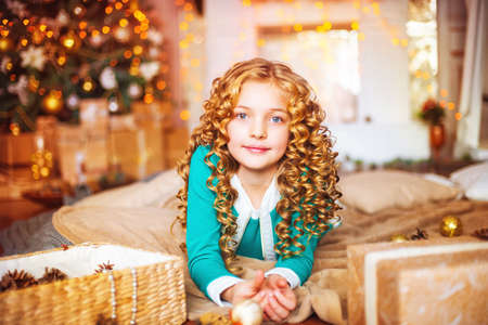 Little girl with long curly hair at home at christmas tree with gifts Stock Photo