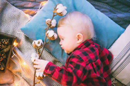 beautiful child lying on the bed on pillows and plaid with a branch of cotton on a background garlands