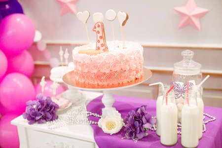 A lovely delicious candy bar in pink and purple colors for a little princess on her 1st birthday. Beautifully decorated childrens party with balloons flowers and sweets Stock Photo