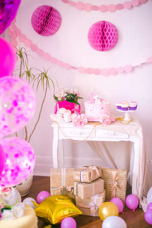 A lovely delicious candy bar in pink and gold colors for a little princess on her 1st birthday. Beautifully decorated children's party with balloons flowers and sweets Foto de archivo