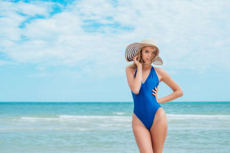Summer vacation happiness carefree joyful sun hat woman with enjoying body weight loss tropical beach destination. Holiday bikini girl relaxing from behind on beach vacation.