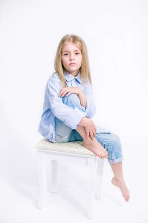 Beautiful fashionable little girl with blond hair in jeans clothes on a white background in studio