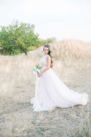 Beautiful young bride with long blond curly hair in a long white dress and bouquet in the summer field Banco de Imagens