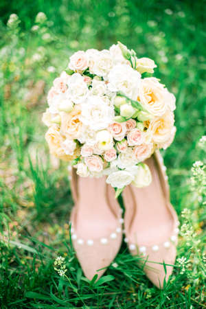 A wedding gentle bouquet of white and pink roses and high-heeled shoes on a green grass in the park. Wedding details