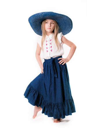 Beautiful fashionable little girl with blond hair in a hat with wide brim and a long fashionable skirt in the studio on a white background