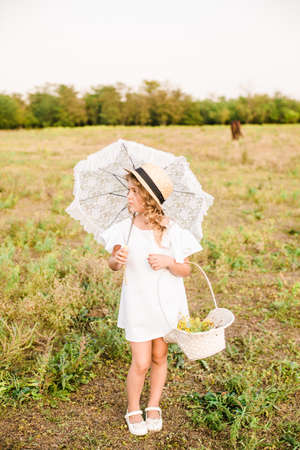 A nice little girl with a light curly hair in a white dress. Rural life in autumn. Horses and people Reklamní fotografie
