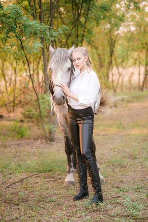 Schönes junges Mädchen mit hellem Haar im einheitlichen Wettbewerb umarmt ihr Pferd: Porträt im Freien am sonnigen Tag auf Sonnenuntergang im Herbst