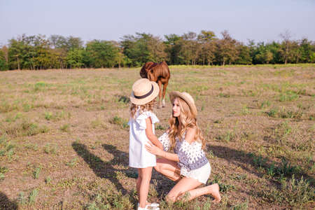 A beautiful young girl, with light curly hair in a straw hat with a little sister hugging and laughing near horses, in the countryside, warm autumn on a sunny day