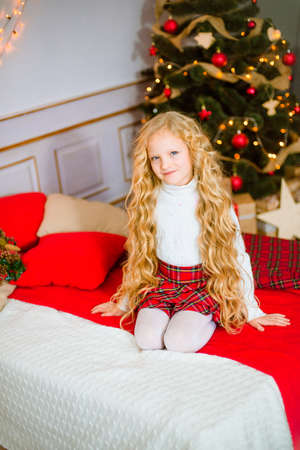 Little girl with blond long hair at Christmas morning. Merry Christmas. Little girl rejoices to the Christmas gift Stockfoto