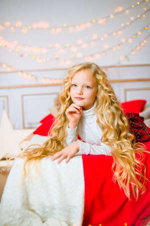 Little girl with blond long hair at Christmas morning. Merry Christmas. Little girl rejoices to the Christmas gift Stock Photo