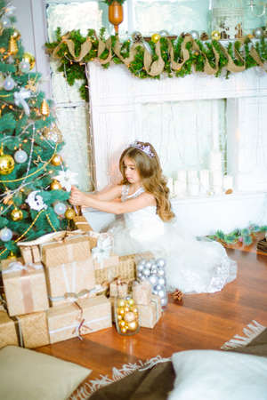 Cute little girl at home near a Christmas tree