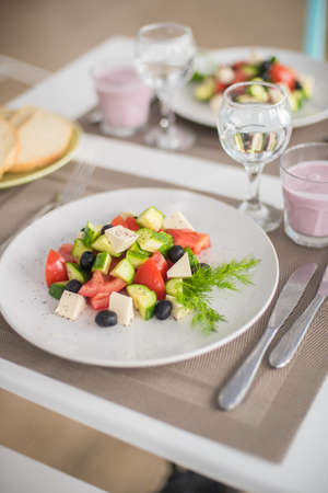Cucumber, tomato, sweet pepper, lettuce, red onion, feta cheese and olives with olive oil. Healthy food, top view Banco de Imagens