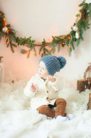 baby with blond curly hair in the christmas decorations