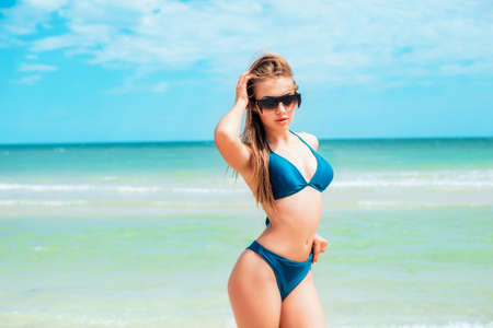 A beautiful young girl with long hair in a blue swimsuit relax on the beach in the sea in sunny hot day