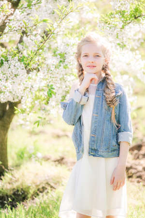 girl in a white sundress in spring Stock Photo