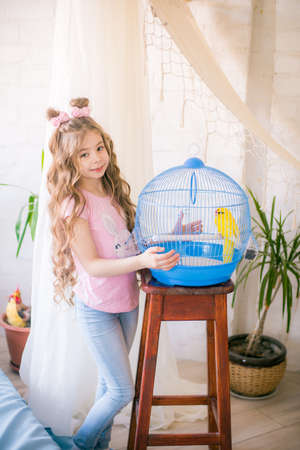 Little cute girl with a cage with a yellow parrot