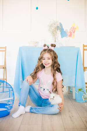Little cute girl with little bunnies and Easter decor at home Stock Photo - 127402284